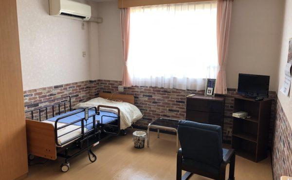 介護ベットとカーテン、家具が付いた居室。清潔感があり広い。