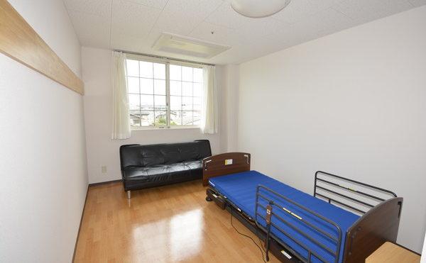 介護ベット、ソファーが付いた居室。布団一式のリースは2,000円(月)で1週間に1回のシーツ交換があります。