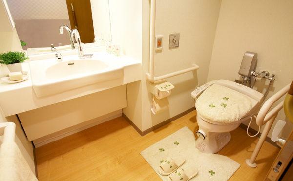 洗面台の蛇口は自動給水。トイレは介助バー、コールボタンがあり、車いすでも十分な広さがあります。